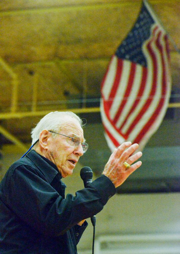 Retired NASA Astronaut Jim Lovell speaks passionately about his time in space, standing in front of an American flag in Bozeman High School gymnasium.