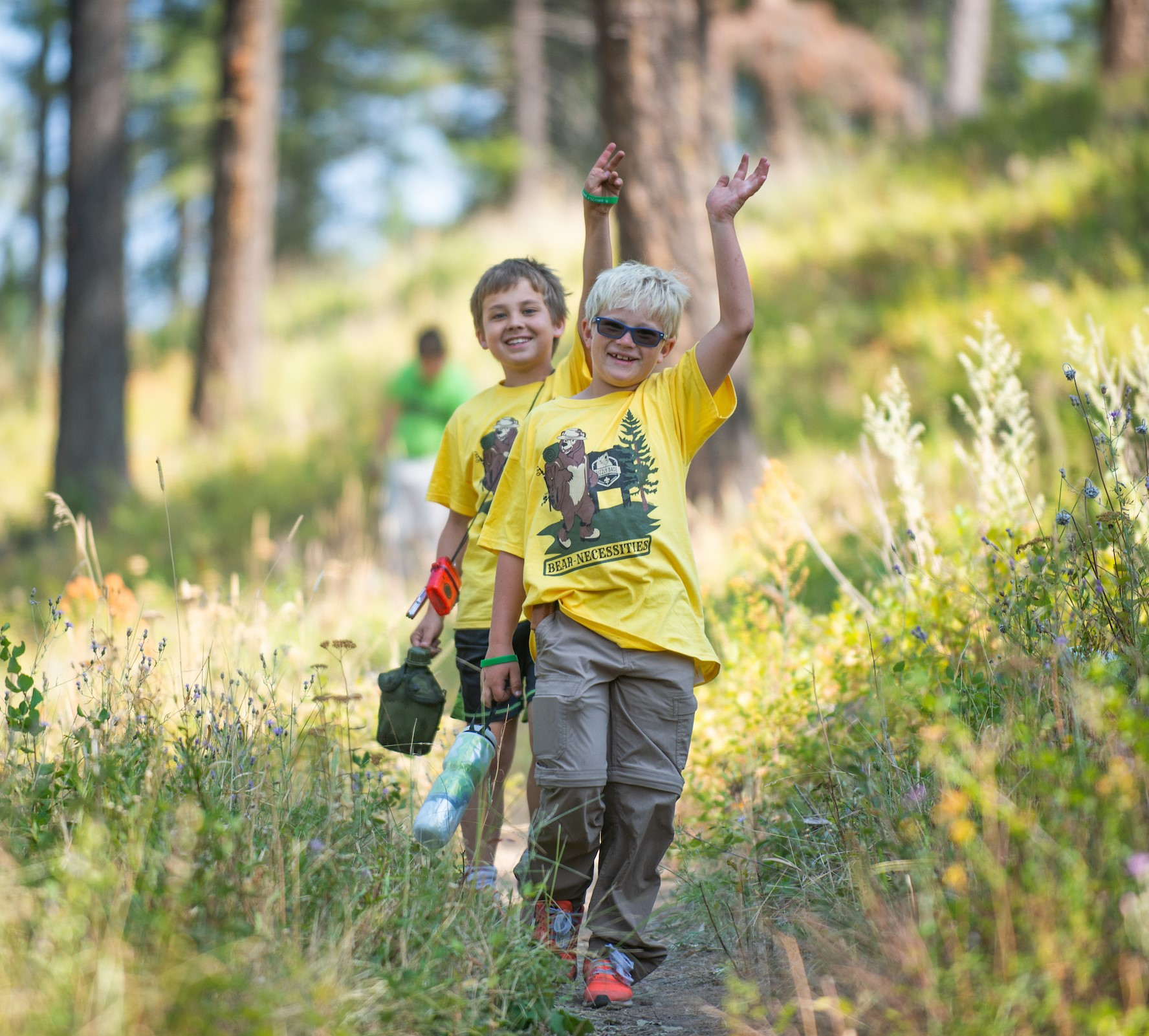 Two Cub Scouts smile as they follow a hiking trail at summer camp.