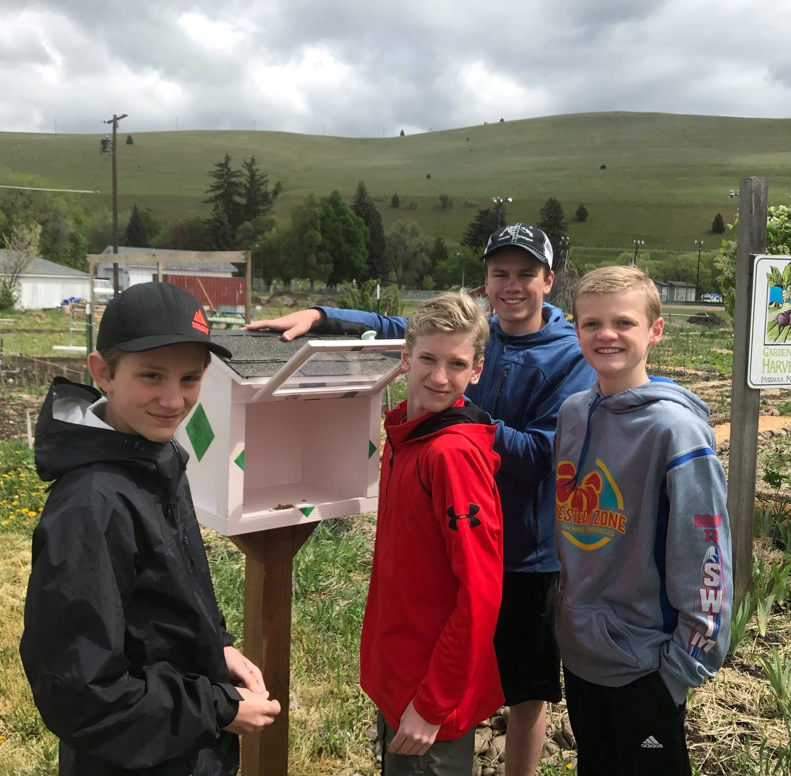 Four Boy Scouts smile after placing a new handcrafted little free library box in front of a community garden as volunteer work.