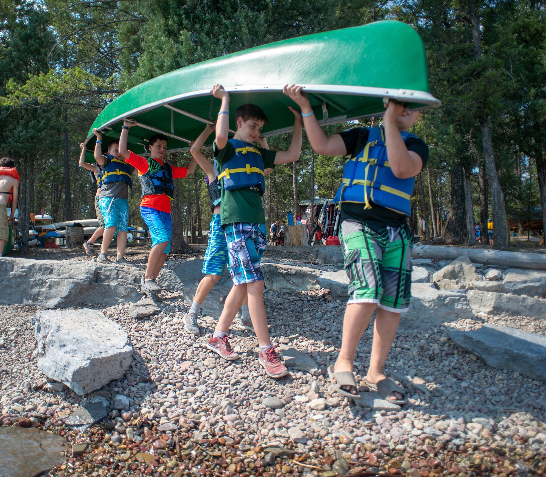 Several Boy Scouts carry a canoe to a lake at summer camp in Montana.